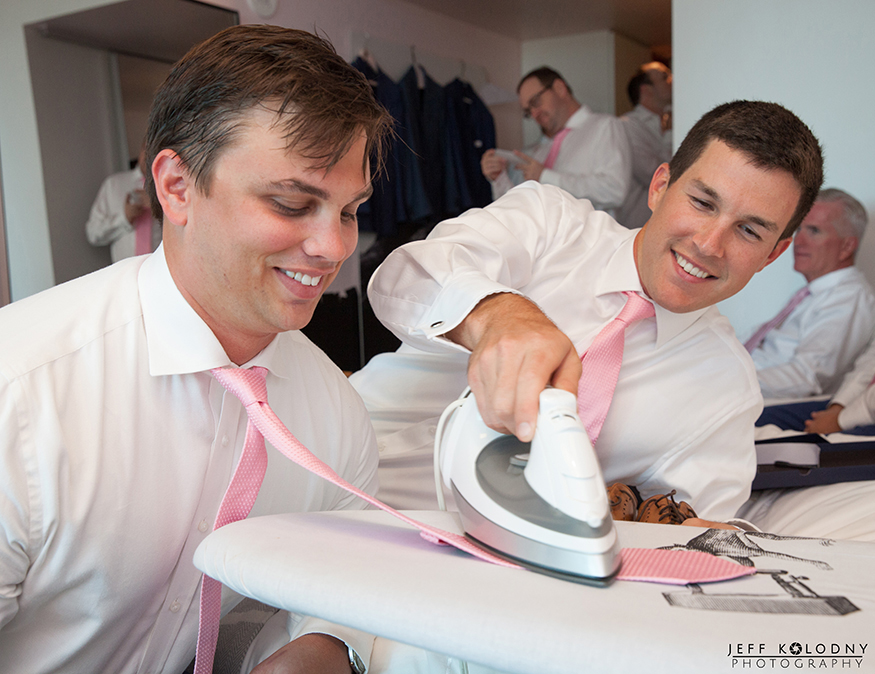 Groomsmen getting ready by ironing each others tie.