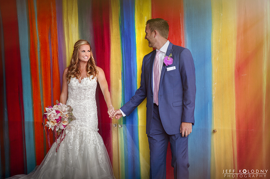 Bride and groom posing in front of a colorful wall at the SLS hotel in Miami.