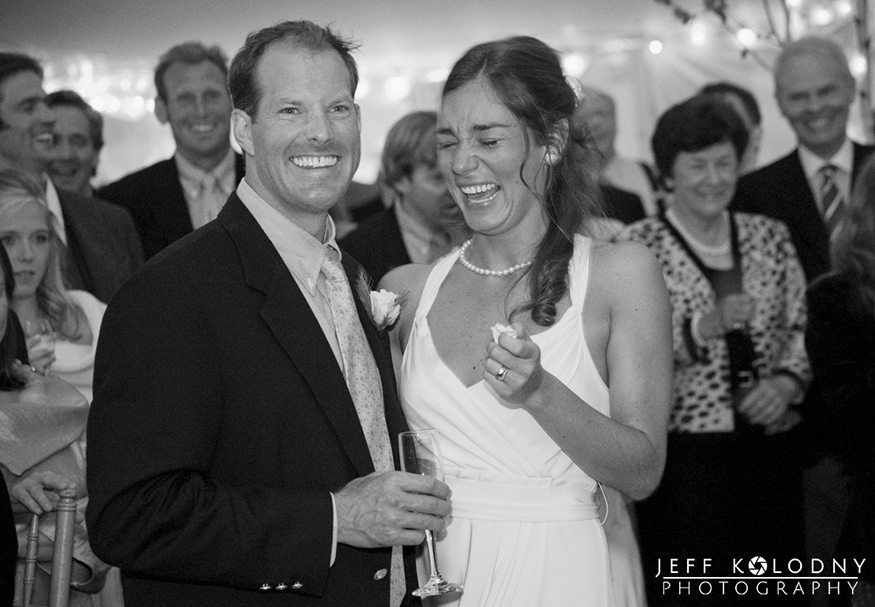 Bride and groom having a laugh during a wedding toast.