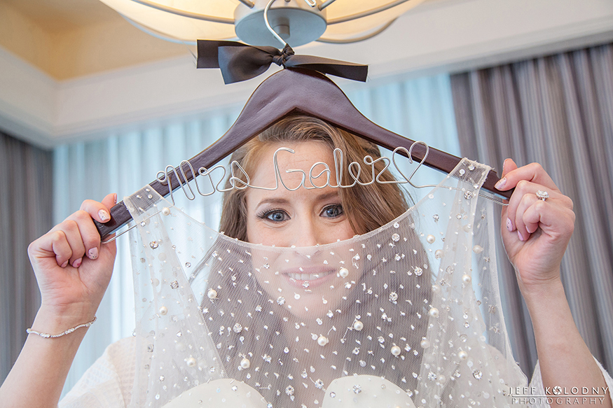 Bride posing with the custom wedding gown hanger.