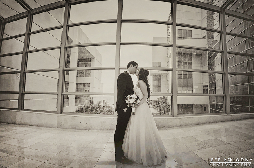 Black and White bride and groom photo taken in the hotel glass walk through between the hotel and ballrooms