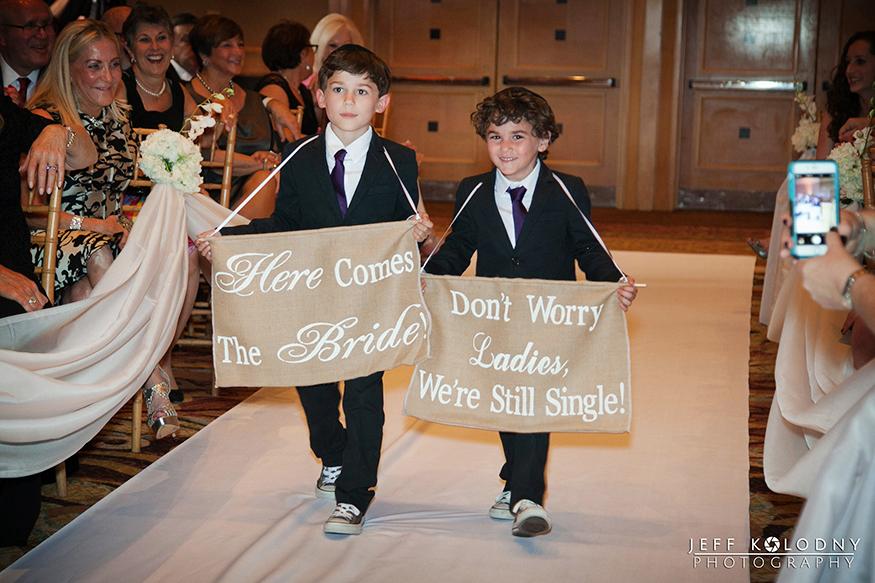 Junior groomsmen walking down the aisle.