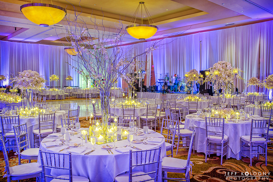 Wedding ballroom decor included branches and flowers for a unique visual experience.