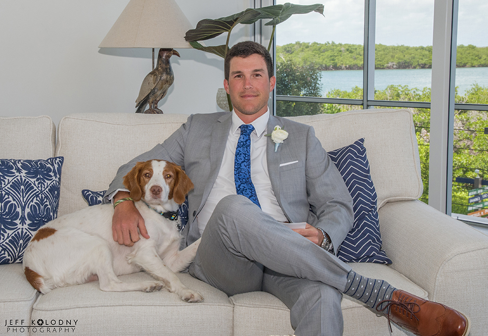 The groom posing with his dog posing at The Ocean Reef Club.