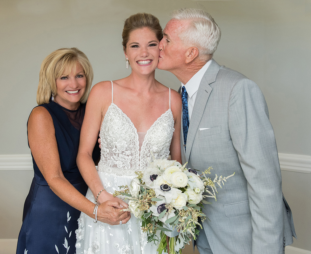 Here the brides father is kissing the brides cheek while mom gives the camera a big smile.