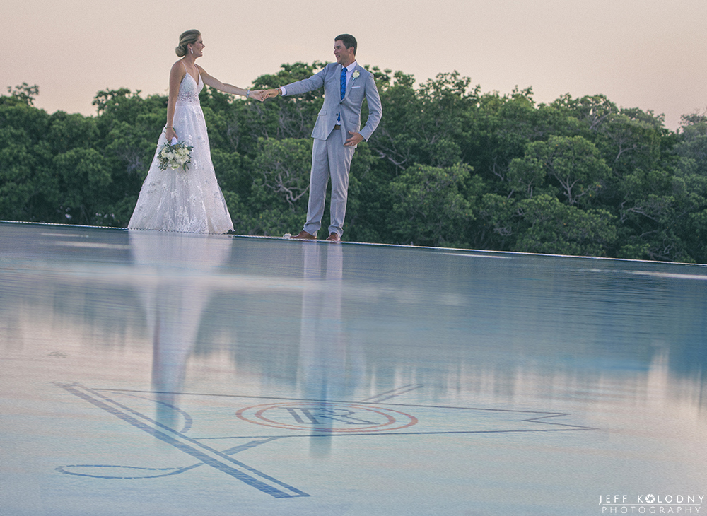 Bride and Groom enjoying a moment by the Ocean Reef Club swimming pool.