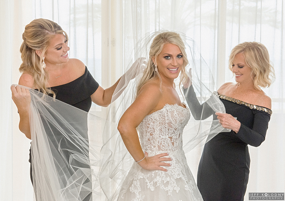 Bride getting ready with the help of her sister and mother at the Eau Palm Beach