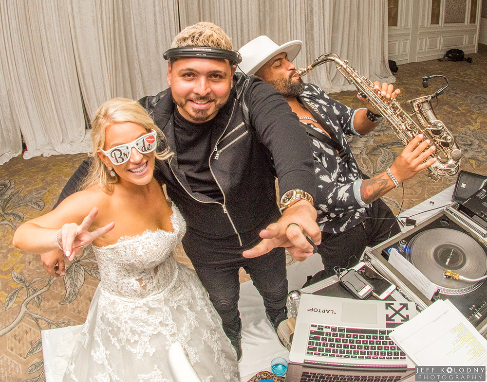 Bride posing with her DJ and Saxophone player at a Palm Beach wedding.