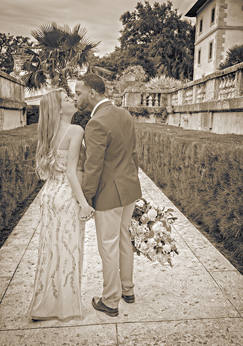 Couple kissing at Vizcaya Gardens and Museum.