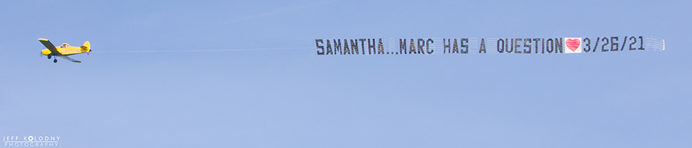 An airplane flying with a banner that reads, Samantha...Marc has a question.