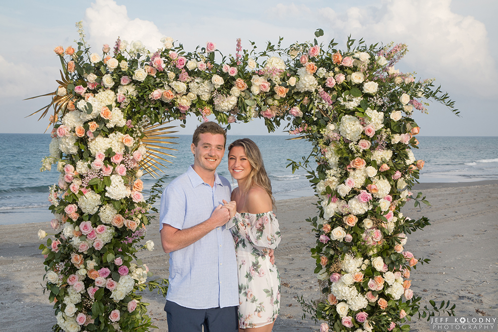 Picture of the soon to be bride and groom surrounded by beautiful flowers.