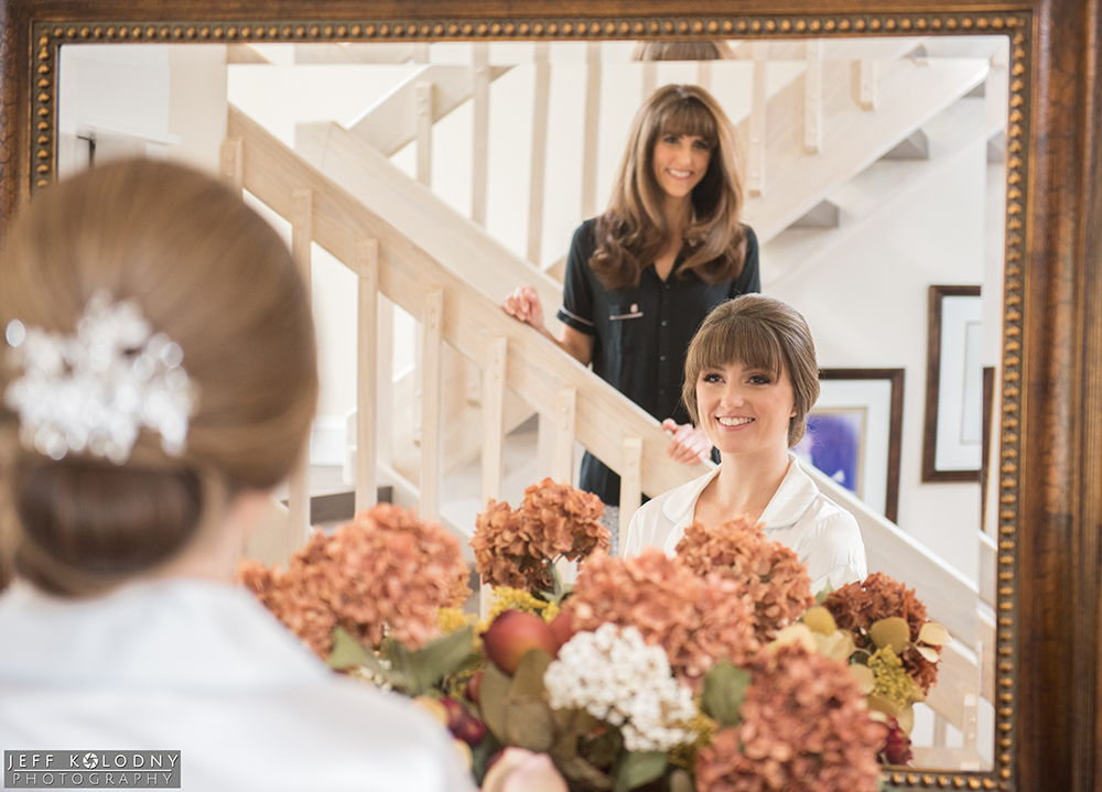 Bride looking in the one of the family home mirrors, with the bride's mother looking from the staircase.