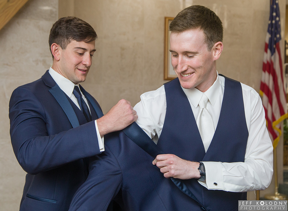 Groom and his best man photo at the church before the ceremony. Here the best man helps the groom with his jacket.