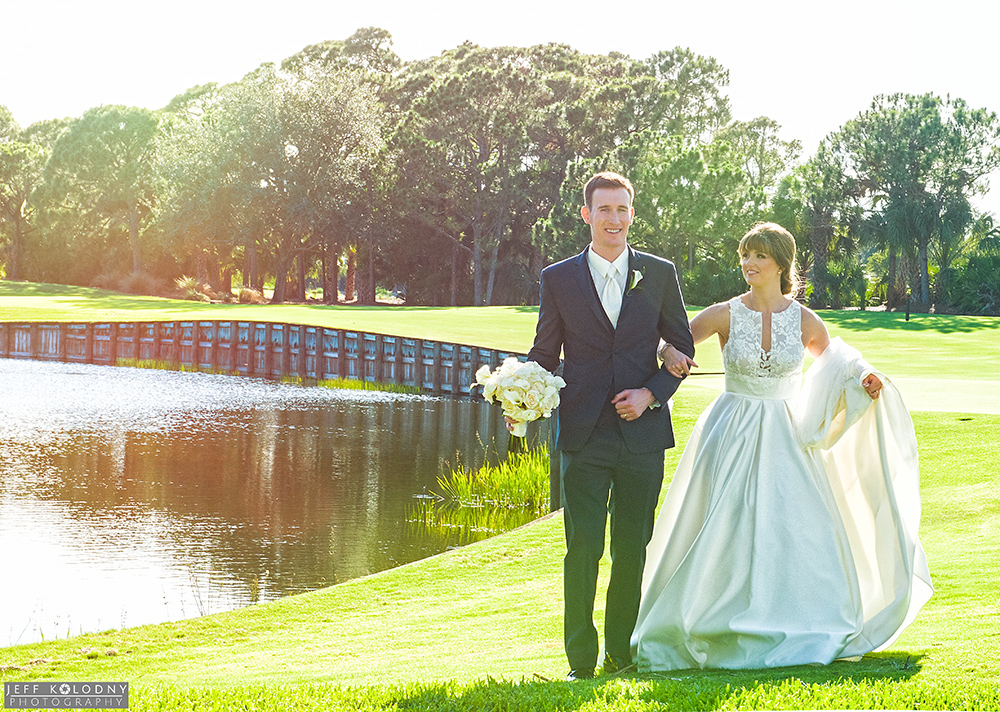 The scenery at the South Florida wedding venue is nothing short of fantastic. Bride and groom walking by lake.