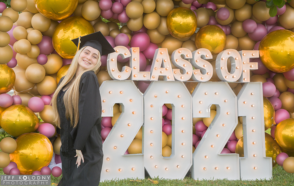 A lovely graduating senior standing in from of a display made with balloons and lights.