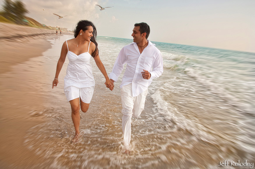 A recently engaged couple running on the beach in Boca Raton.