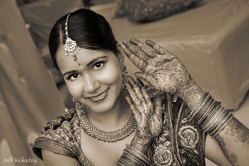 Sepia picture of a bride showing off the henna on her hands.